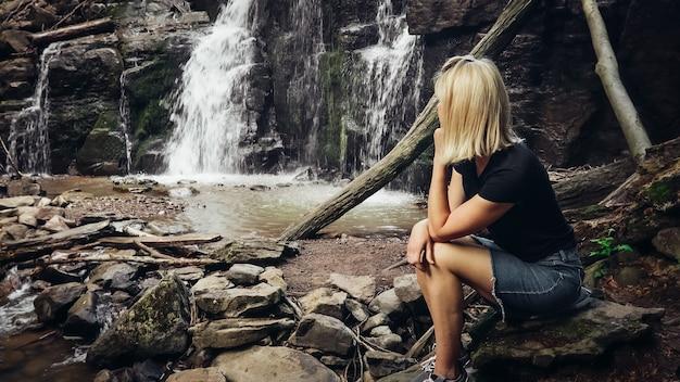 Ragazza seduta vicino alla cascata e gode dei suoni dell'acqua