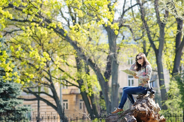 Ragazza che si siede nel parco e leggendo una mappa