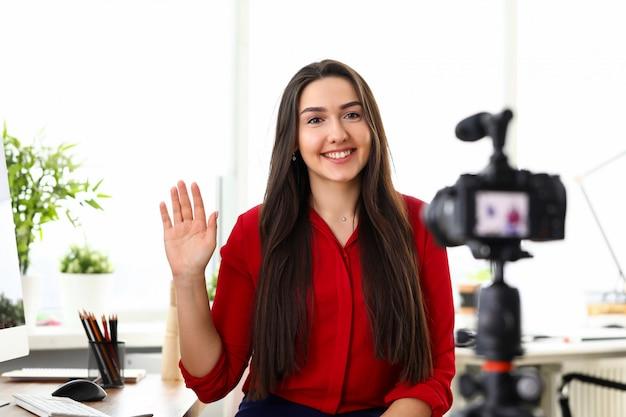 Sorrisi di seduta della ragazza alla macchina fotografica