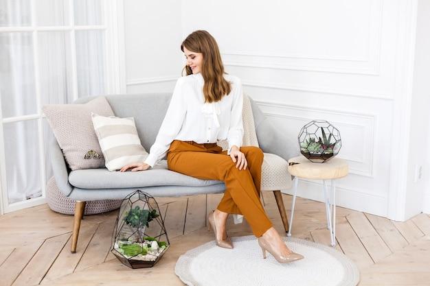Ragazza seduta sul divano interni luminosi, accanto a forma di vetro per piante, decorazione d'interni