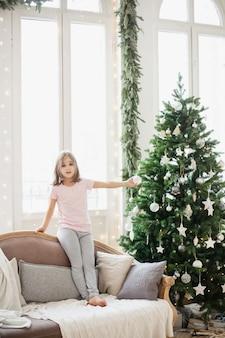Ragazza seduta sul divano di casa durante il natale