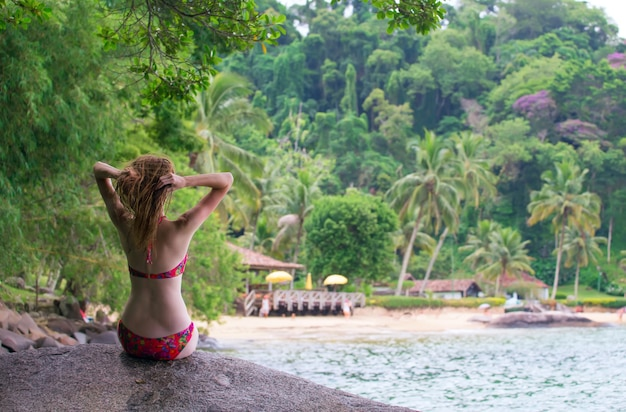 Ragazza seduta su una pietra e guardando la piccola spiaggia brasiliana