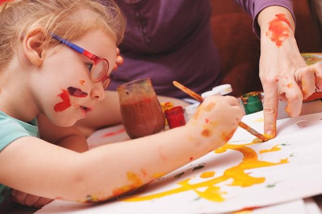 Ragazza seduta al tavolo e disegna i colori