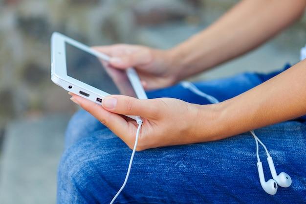 Ragazza che si siede con un tablet nelle mani