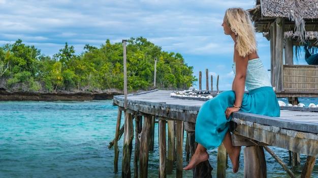 Ragazza seduta sul molo in legno di una famiglia guardando nell'oceano blu, capanna di bambù, isola di gam, papua occidentale, raja ampat, indonesia