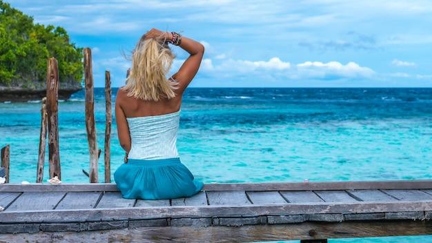 Ragazza seduta sul molo in legno di una famiglia guardando nell'oceano blu, gam island, papua occidentale, raja ampat, indonesia