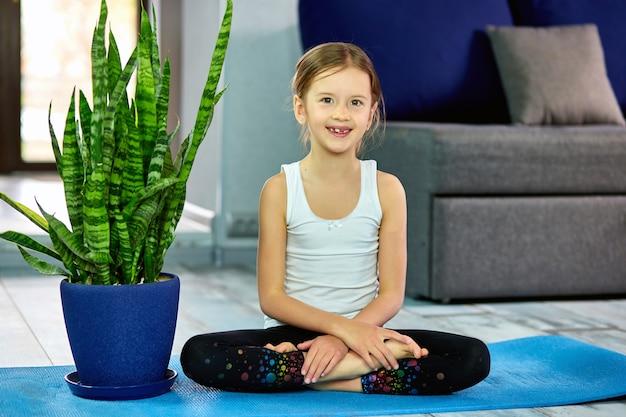 Una ragazza seduta in asana yoga su una superficie blu. il concetto di formazione domestica, yoga per bambini.