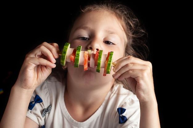 Una bambina di sei anni mangia un insolito panino su un bastoncino. cetriolo, pomodoro, salsiccia