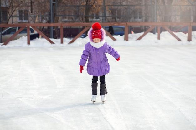 Una ragazza pattina su una pista di pattinaggio sul ghiaccio in inverno. pista di pattinaggio nel cortile della città. il bambino impara a pattinare