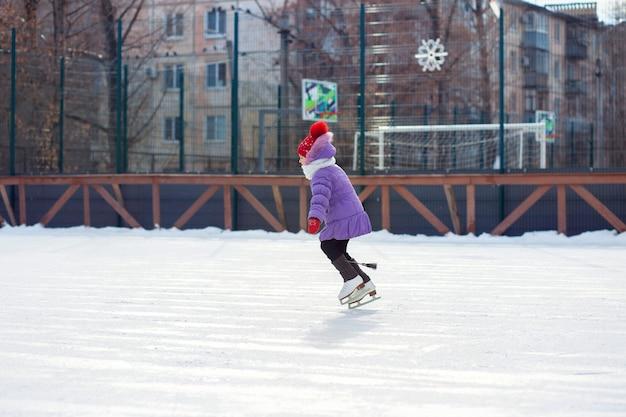 Ragazza che pattina in inverno su una pista di pattinaggio in città
