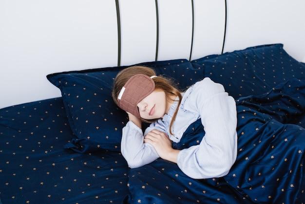 La ragazza dorme e giace in pigiama in un lino bianco. letto blu. benda sulla testa. maschera per dormire.