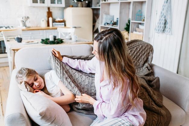 Una ragazza dorme sul divano, sua madre ruba una coperta per sua figlia, cura e attenzione, natale