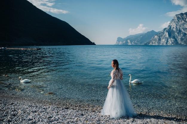 Una ragazza in un elegante abito bianco cammina lungo l'argine del lago di garda, una donna è fotografata sullo sfondo di una montagna e di un lago in italia.torbole.
