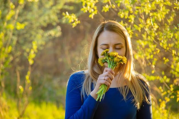 La ragazza che odora i fiori nel campo