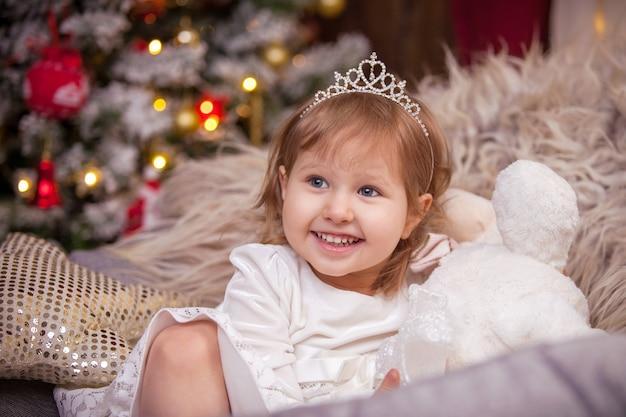 La ragazza sorride, un albero di natale tra le luci e una finestra con una ghirlanda avvolge l'atmosfera della vacanza