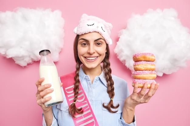 La ragazza sorride felicemente gode di trascorrere il tempo libero a casa tiene una pila di gustose ciambelle glassate e latte fresco ha un debole per i dolci avrà una deliziosa merenda pose al coperto