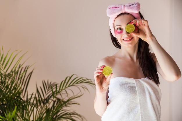 La ragazza sorride guarda la telecamera chiude gli occhi con una metà del lime che tiene l'altra metà in mano