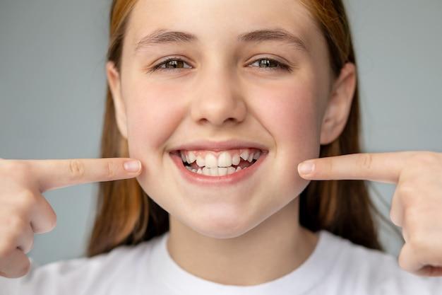 La ragazza sorride e mostra i suoi denti irregolari con le sue mani medicina dentale e assistenza sanitaria