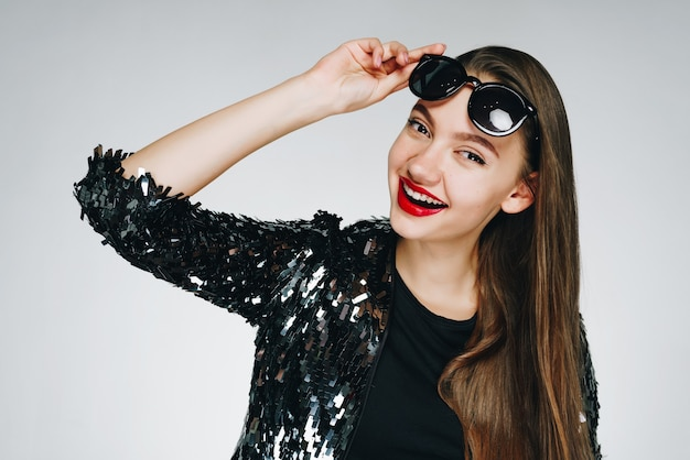 La ragazza sorride trionfante tenendo gli occhiali sulla fronte con la mano. sfondo chiaro