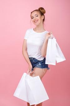 La ragazza sorride con le borse bianche del mestiere in sue mani su uno spazio rosa. shopping. bayer