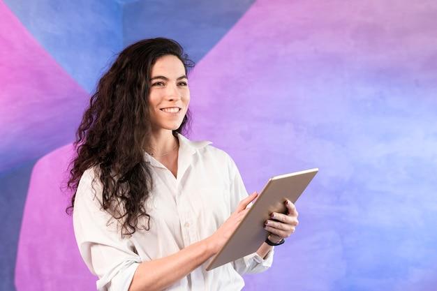 La ragazza sorride e scrive sulla compressa digitale