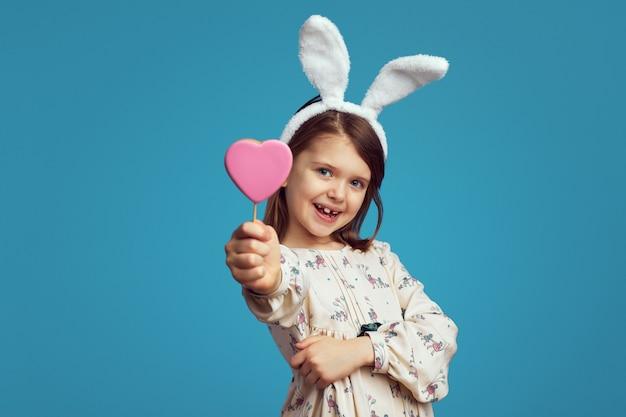 Ragazza sorridente e con in mano un biscotto a forma di cuore con orecchie da coniglio