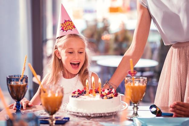Ragazza sorridente e guardando la sua gustosa torta di compleanno