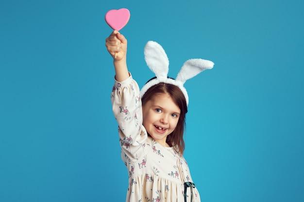 Ragazza sorridente e alzando un gustoso biscotto a forma di cuore dolce che indossa orecchie da coniglio