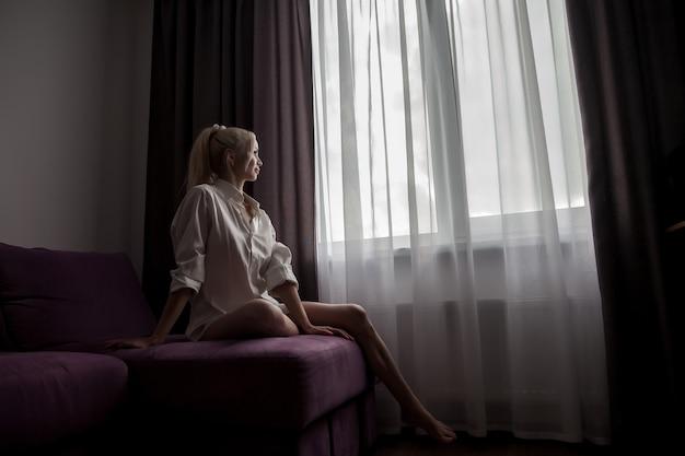 Ragazza sul divano alla finestra della casa in attesa alla luce del sole dalla finestra. ritratto di bella donna. comfort domestico e intimità. femmina slava in mattinata in camera. emozioni e relax. concetto di relax domestico