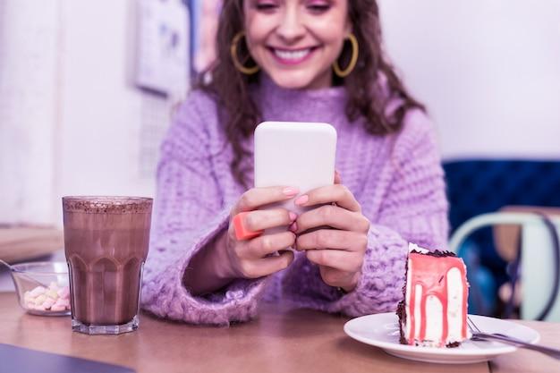 Ragazza di trascorrere del tempo. sorridente signora positiva che controlla i suoi social media mentre è seduto in un caffè con un bicchiere di cacao e torta
