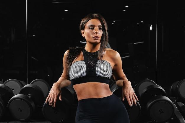 Ragazza in un palazzetto dello sport in posa sulla fotocamera, un bellissimo modello di fitness in posa sulla fotocamera mentre era seduto su un'attrezzatura sportiva