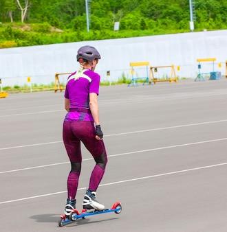 La ragazza sportiva cavalca sugli sci a rotelle sull'asfalto