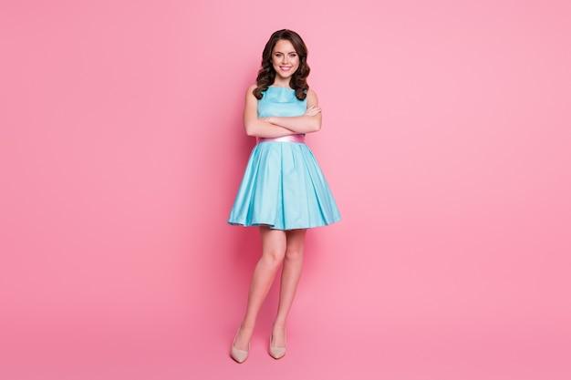 La ragazza sta dritta isolata su uno sfondo di colore rosa pastello