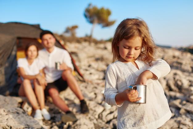 Ragazza in piedi sulla spiaggia e mettendo la mano nella tazza.
