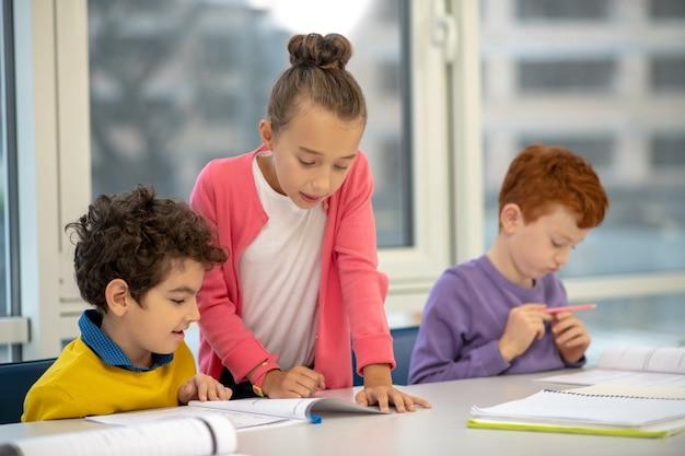 Ragazza in piedi tra i ragazzi della sua classe