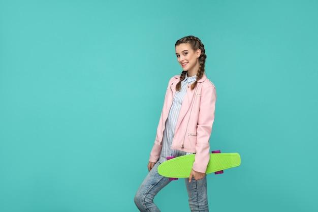 Ragazza in piedi e tenendo lo skateboard e guardando la telecamera con un sorriso a trentadue denti