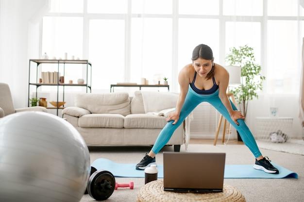 Ragazza in piedi al computer portatile, allenamento fitness online a casa. persona di sesso femminile in abbigliamento sportivo, allenamento sportivo internet, interno della stanza
