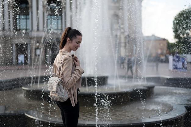 Ragazza in piedi vicino alla fontana. weekend in europa. uno spruzzo d'acqua.