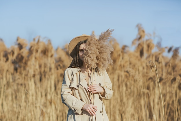 Ragazza in piedi in un campo di canne e nascondendo metà faccia dietro rami di canna alta