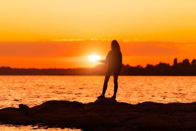Ragazza in piedi sulla roccia che tiene il sole a portata di mano. natura e concetto di bellezza. tramonto arancione. siluetta della ragazza al tramonto.