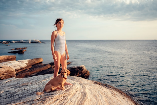 Ragazza che sta sulla spiaggia rocciosa con un cane vicino al mare