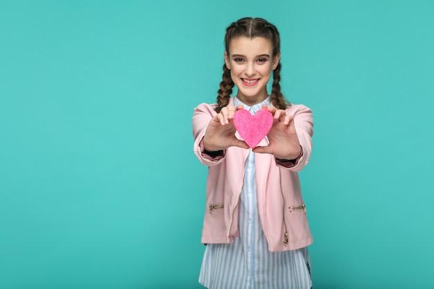 Ragazza in piedi e mostrando la forma del cuore rosa e guardando la telecamera con un sorriso a trentadue denti