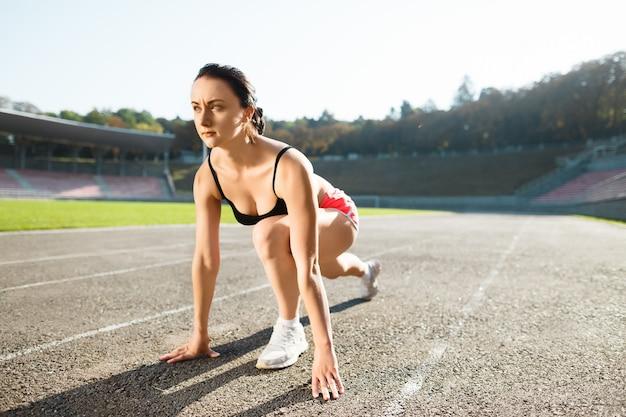 Ragazza in piedi sul punto di partenza sullo stadio prima di correre in pista. giovane donna in top nero, pantaloncini rosa e scarpe da ginnastica bianche pronte per la corsa. all'aperto, sport