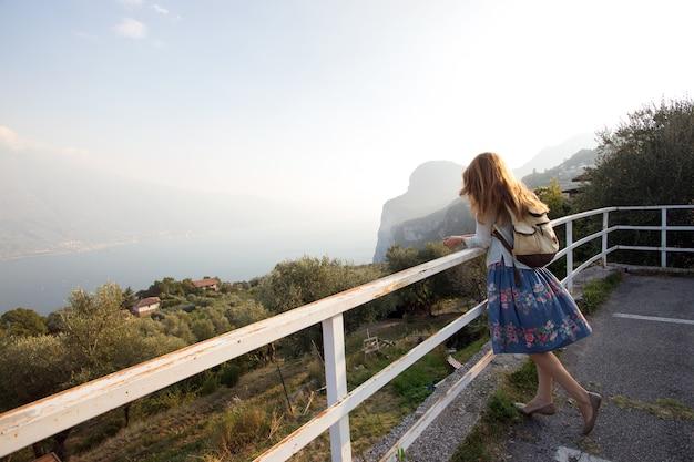 Ragazza in piedi sulla piattaforma panoramica e guarda il lago di garda. italia