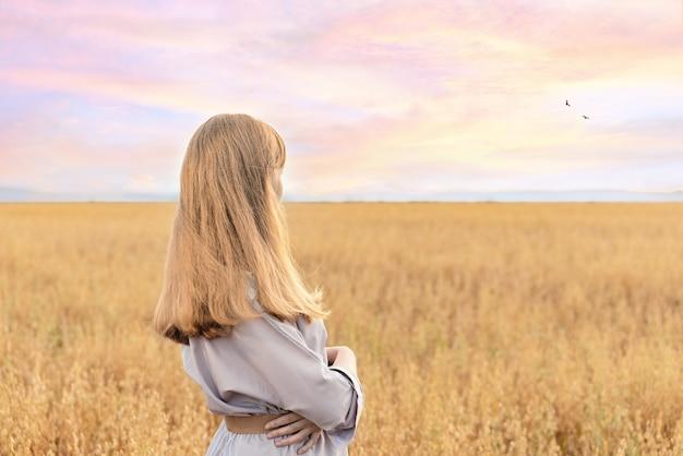 Ragazza in piedi in un campo di grano con un grande tramonto sullo sfondo