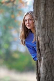 La ragazza sta alla base di una grande quercia