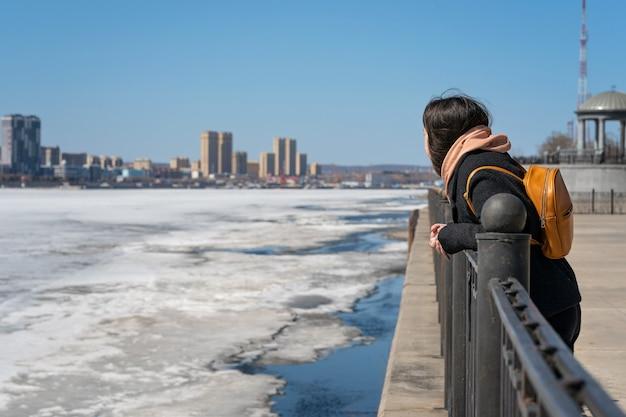 La ragazza sta sull'argine e guarda la città dall'altra parte e il ghiaccio sul fiume