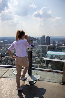 La ragazza si trova su un'alta torre nella città di frankfurn on main e guarda la città