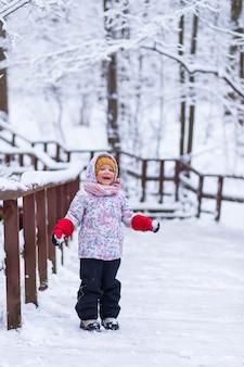 Una ragazza sta vicino alla ringhiera nella foresta invernale