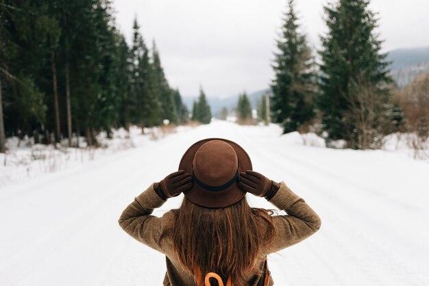 Una ragazza si trova su una strada forestale innevata, una vista dal retro